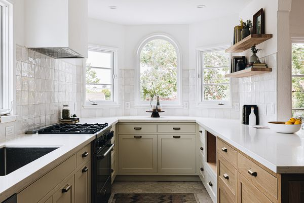 Cabinets painted tan in kitchen with white walls and wooden shelving
