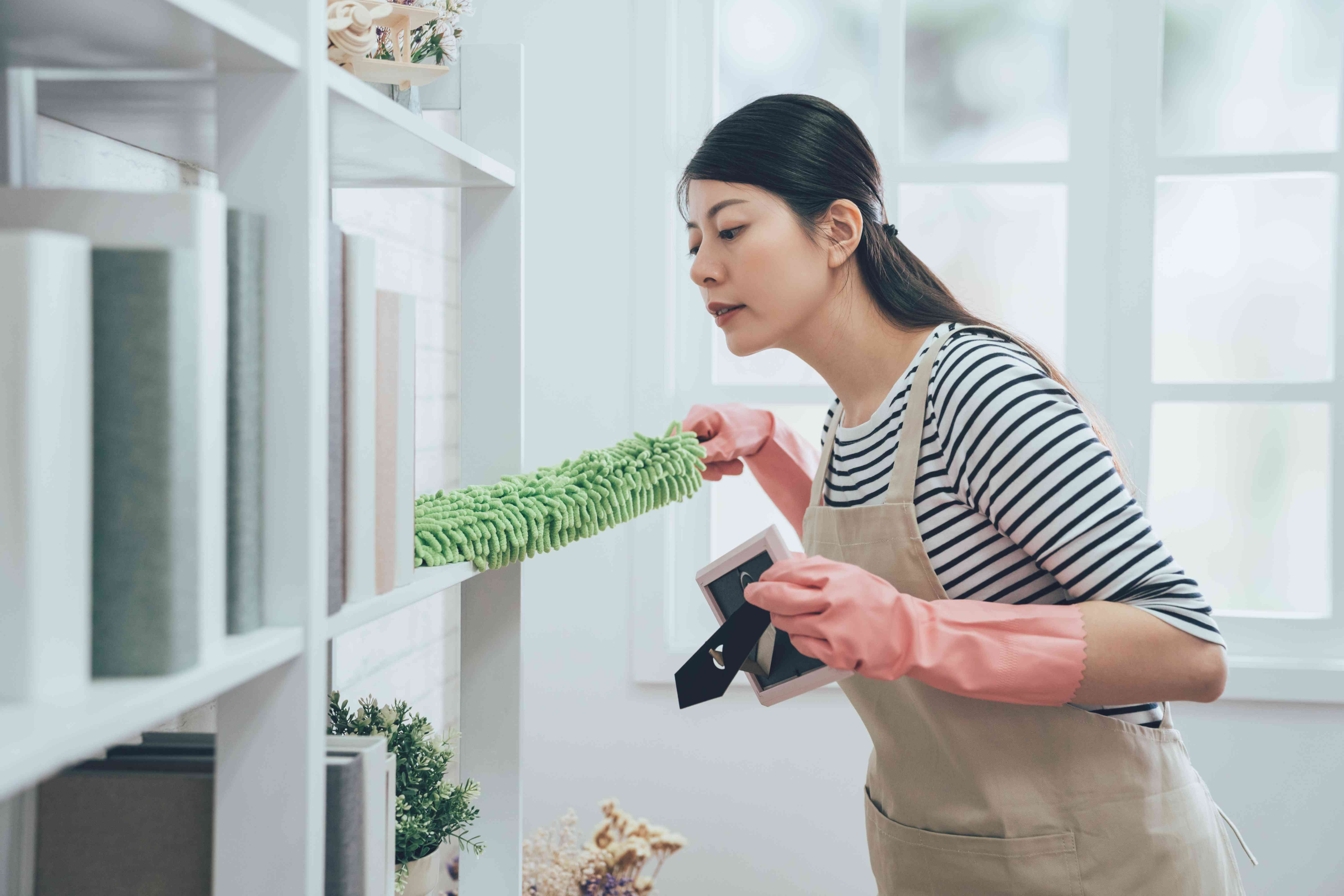 asian housekeeper in apron dusting the bookshelf