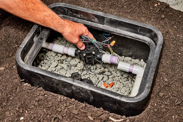Lawn irrigation valve box exposed showing pipe and valve with wires