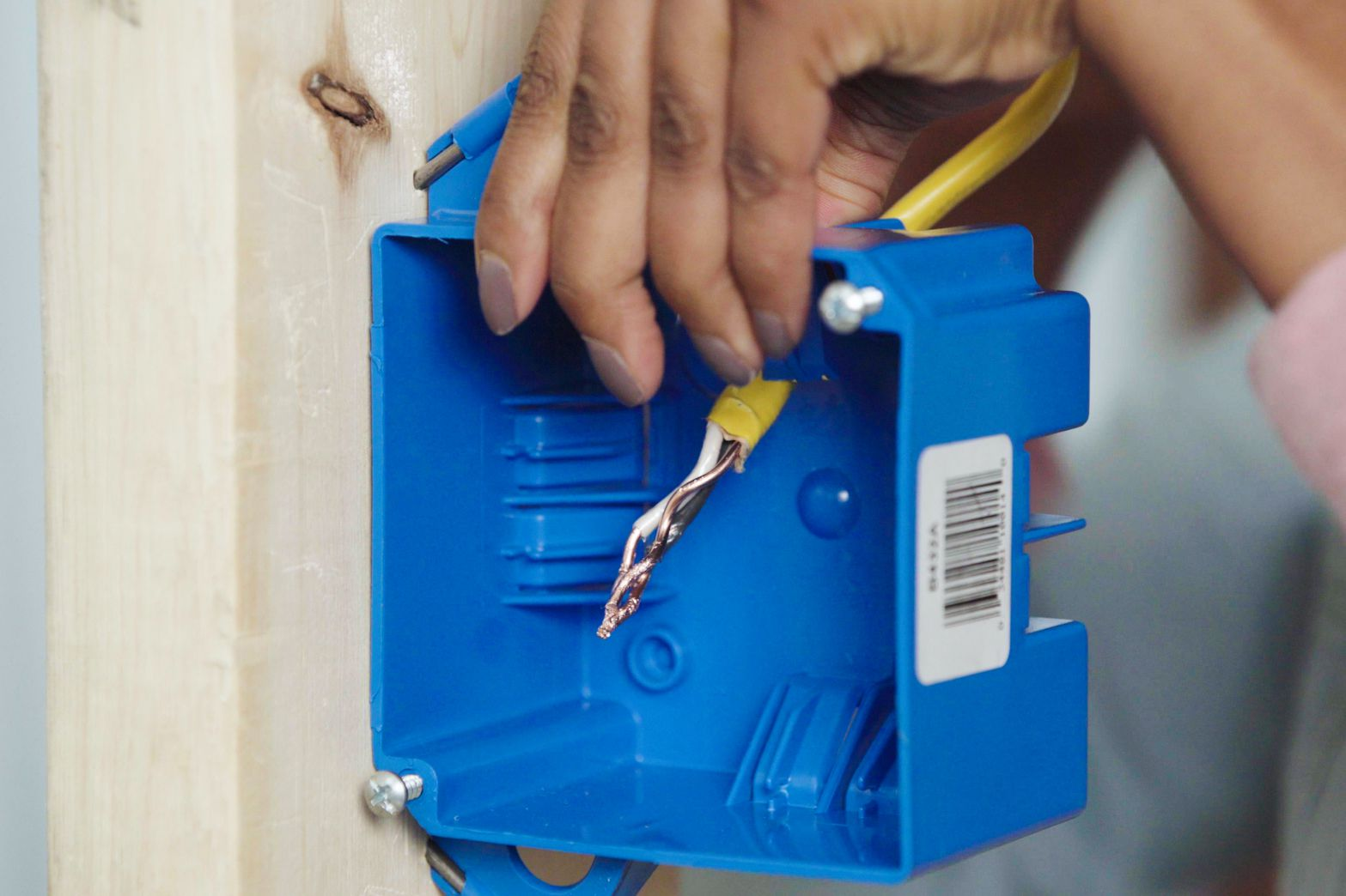 End cables clamped inside blue electrical junction box