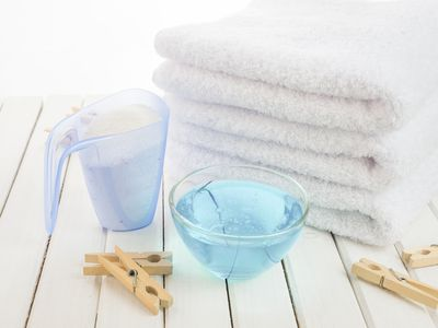 Bath towels, washing powder, fabric softener and wooden clothespins