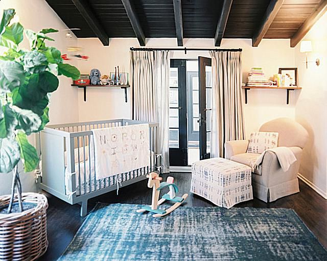 A simple white nursery with rich wood floors and ceiling.