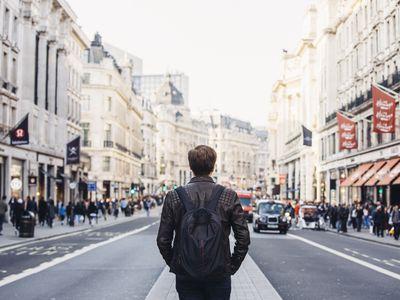 Tourist with backpack walking on Regent Street in London, UK