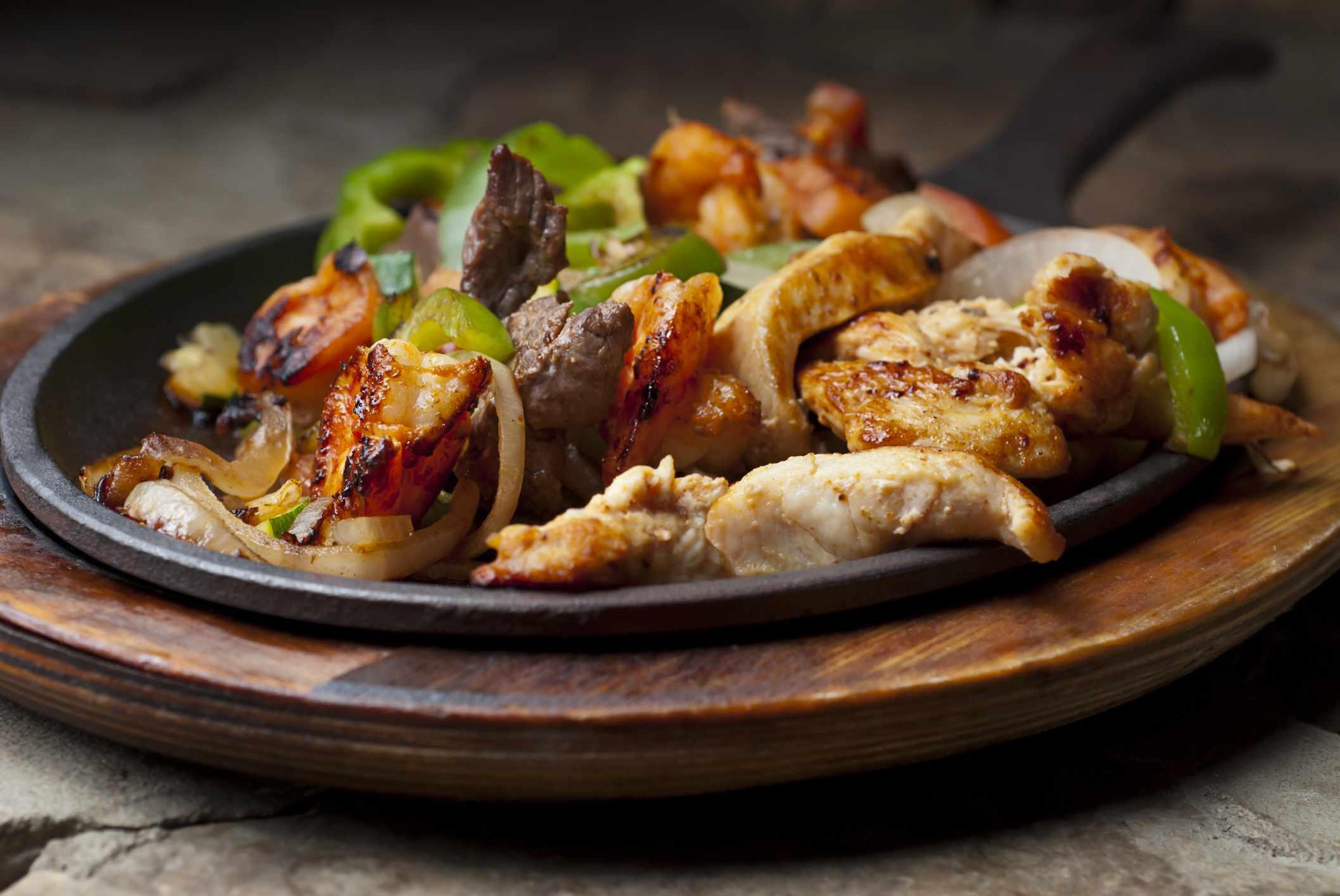 A skillet of chicken and shrimp fajitas.