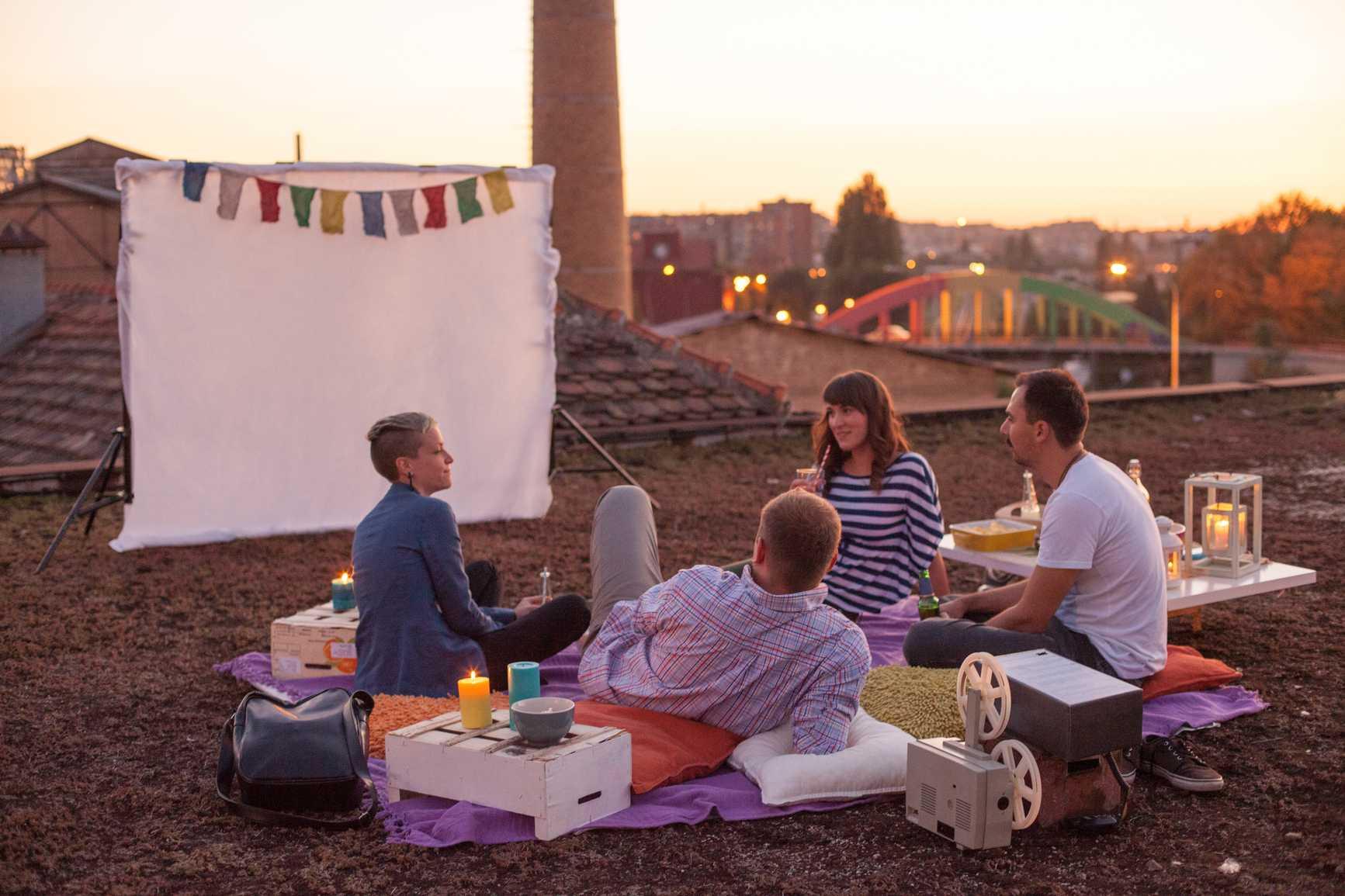 people with a backyard movie screen setup