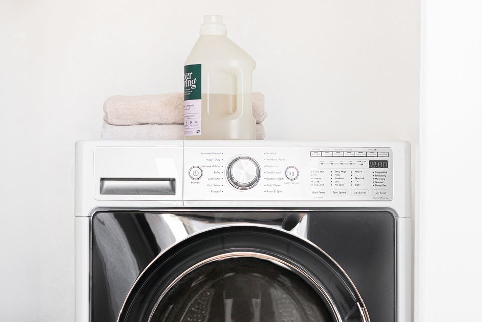 Top of white and black combination washer and dryer machine with laundry detergent and folded towels on top