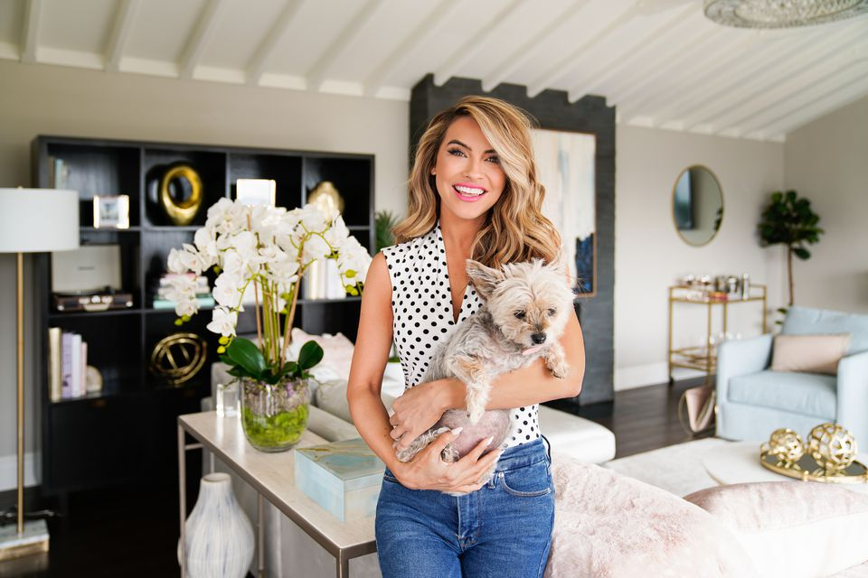 Chrishell Stause poses with her dog in her newly redecorated living room featuring items from T.J.Maxx and Marshalls