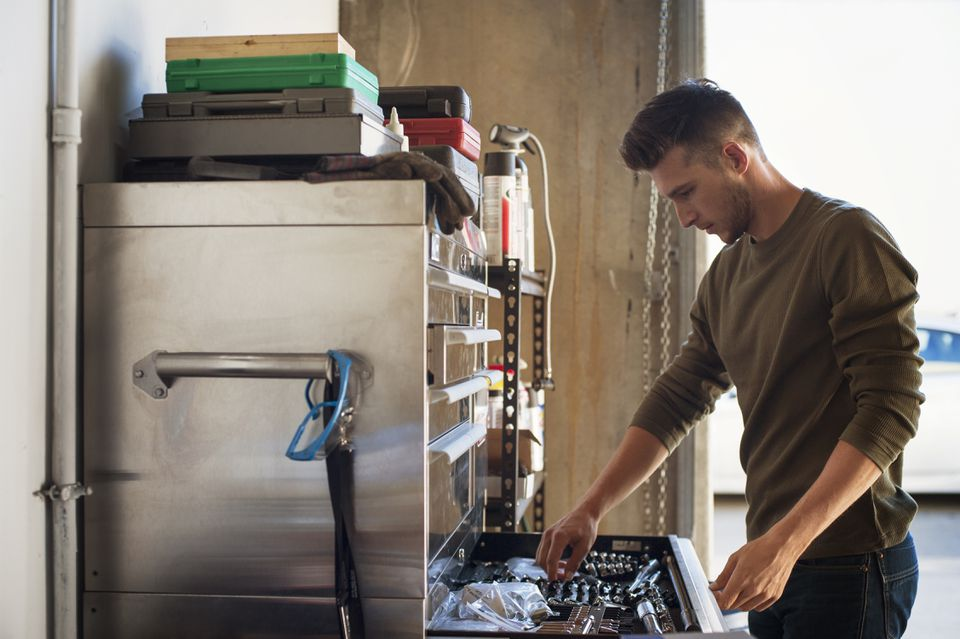 Side view of man taking work tools from cabinet in garage