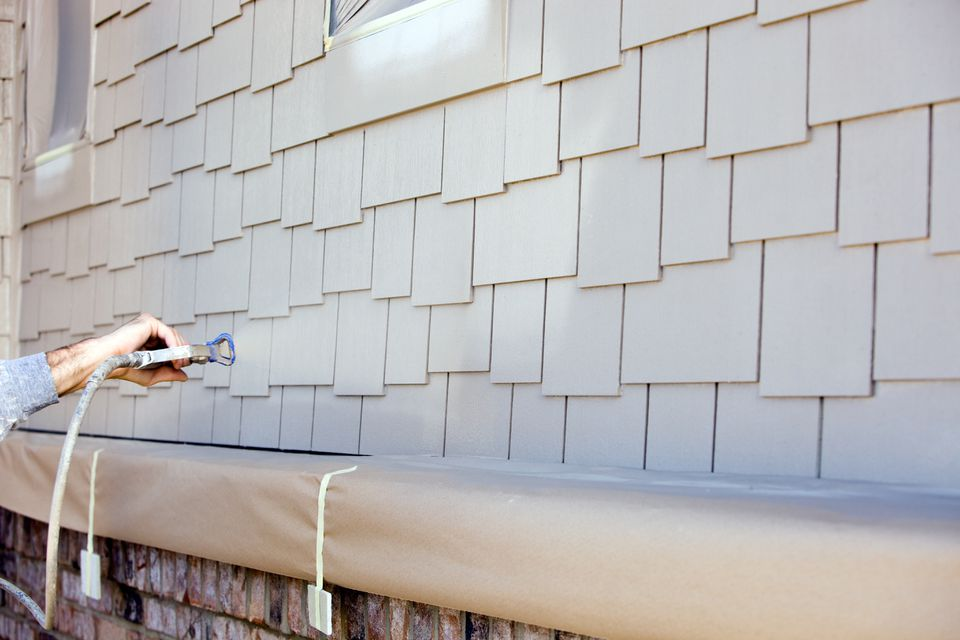 House Painter Spraying Paint on New Siding