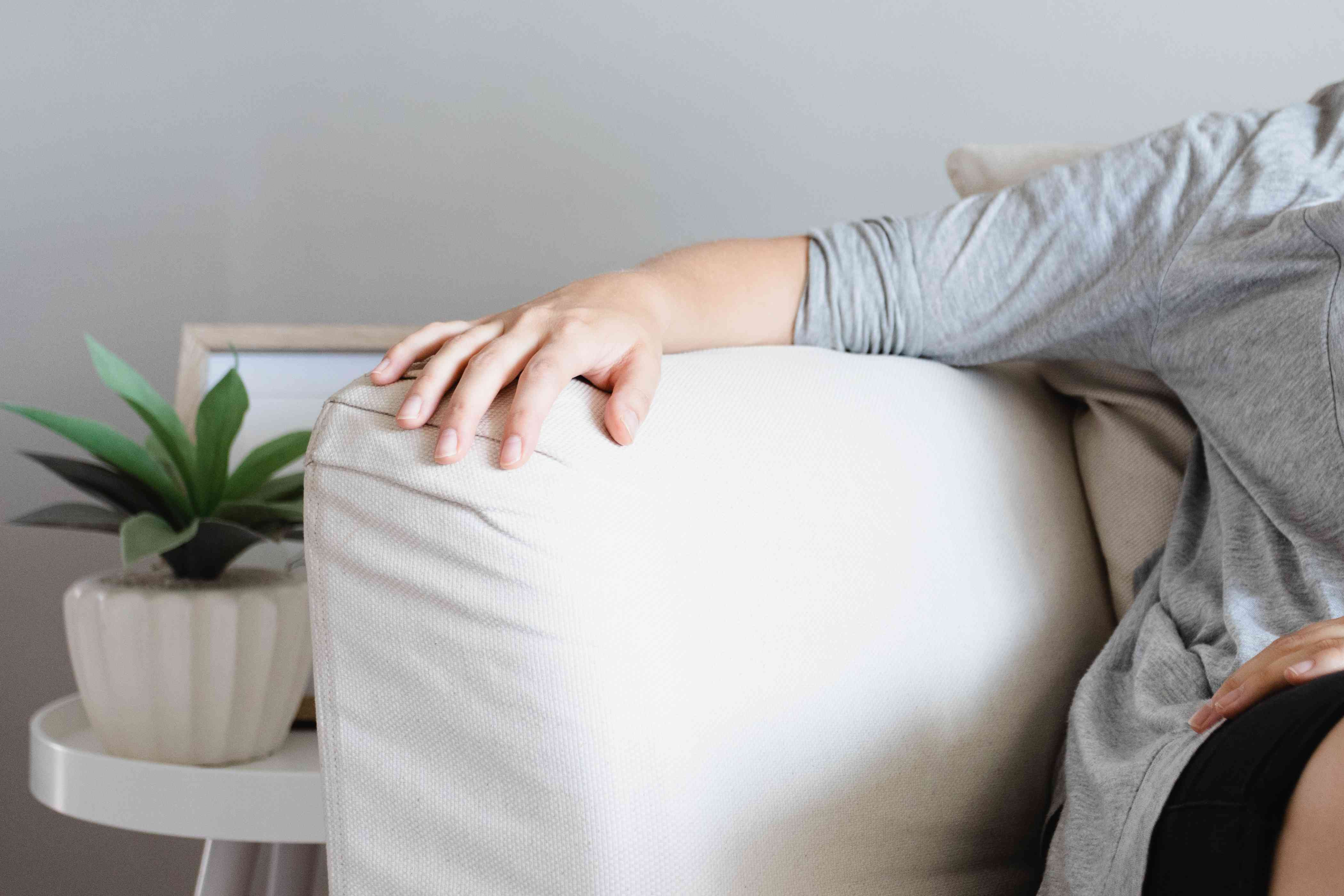 Arm resting on white couch arm next to side table with plant