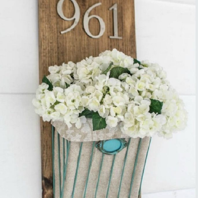 A wooden address sign with white faux flowers underneath.