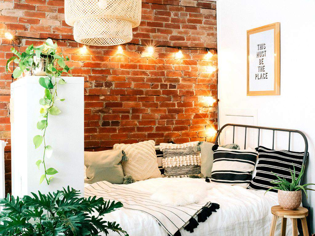 room with a bed and lights and a brick wall