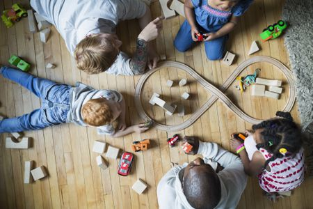 Overhead View Fathers And Children Enjoying Play Date Playing With Toy Train Wood Blocks