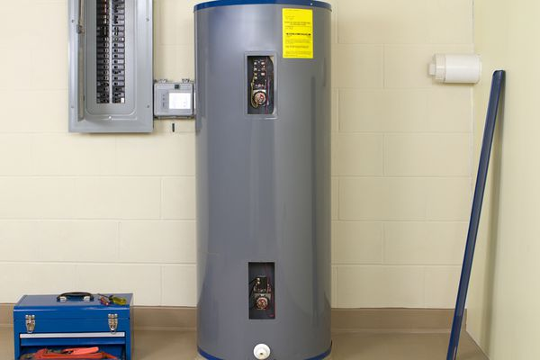 Residential water heater next to circuit breaker and toolbox