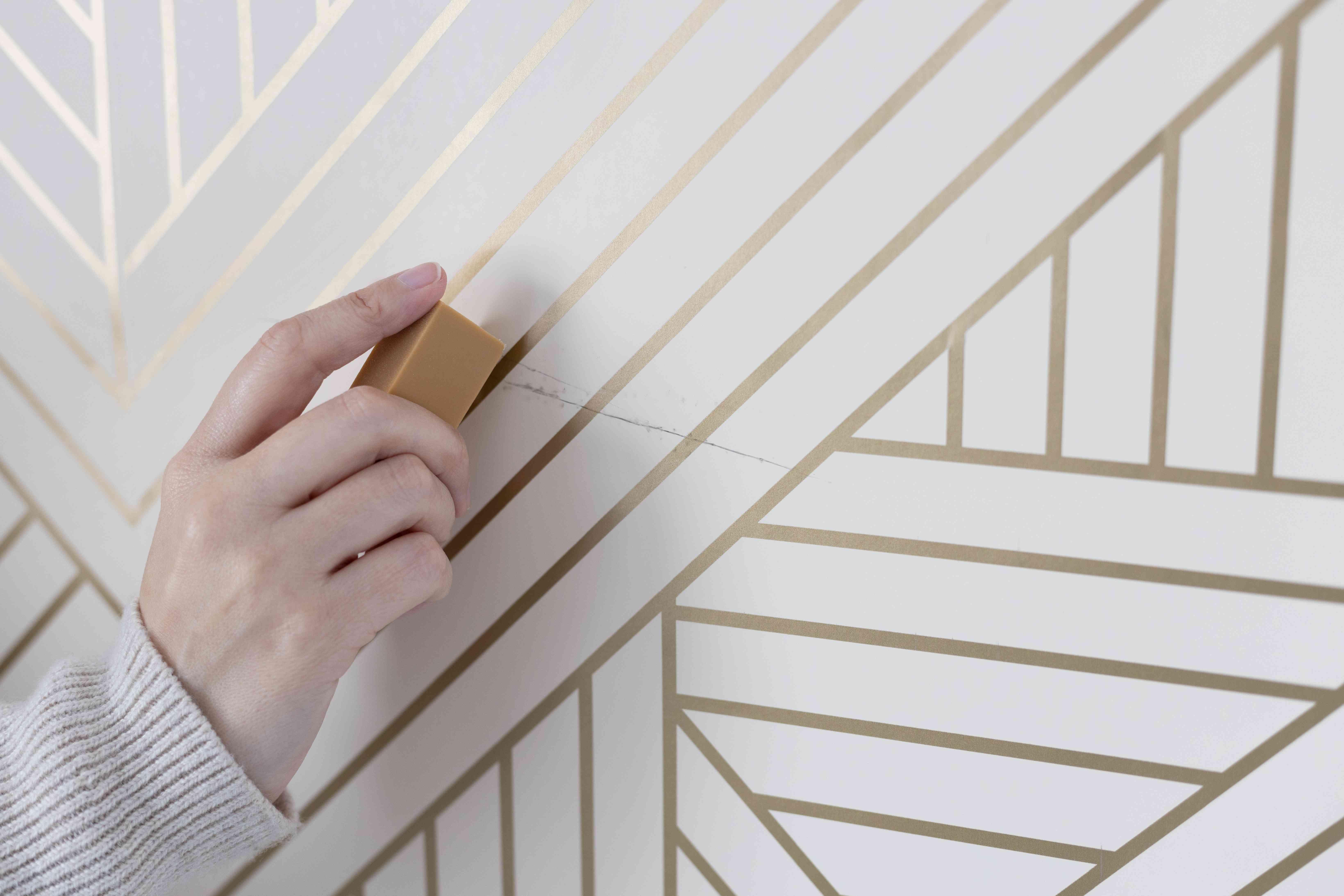 Art gum eraser removing scuff mark on white and gold striped wallpaper