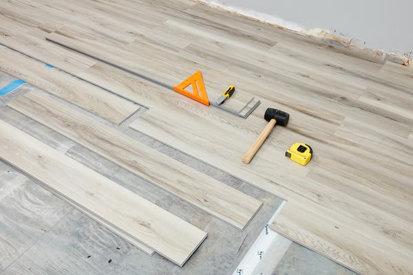 Vinyl plank flooring being installed with tools laid on ground