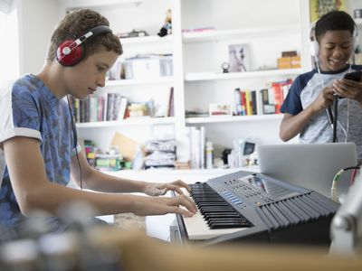 Teenage boy with headphones playing keyboard piano in home office