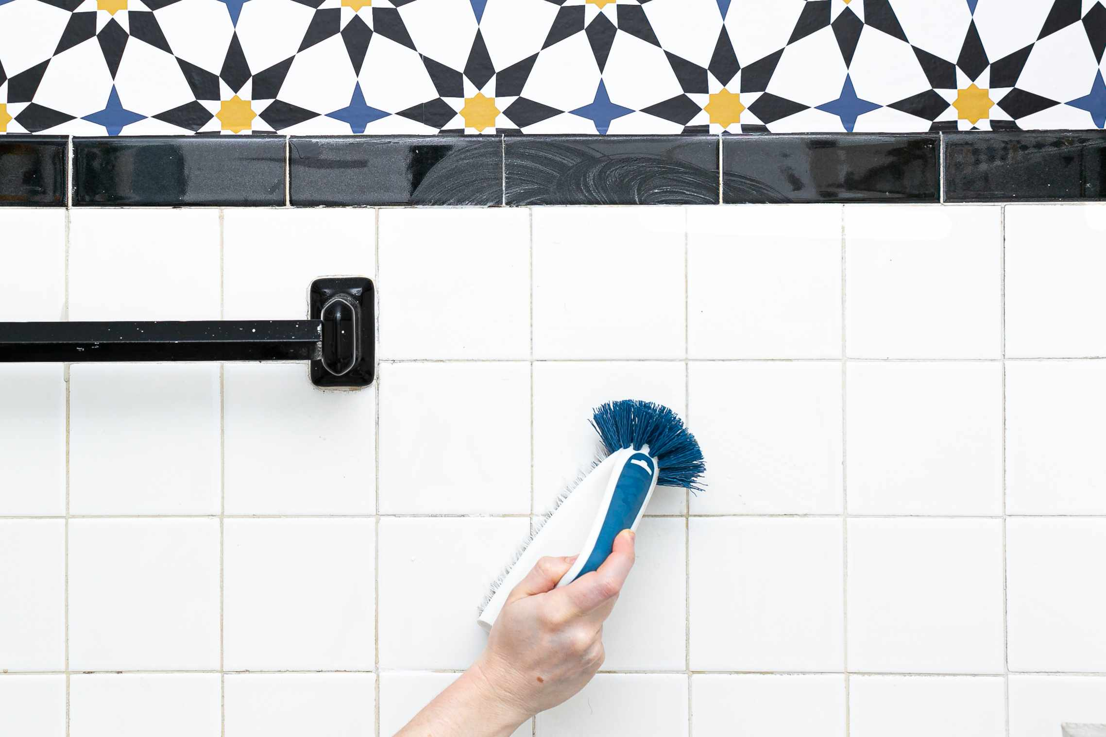 using a grout brush to scrub