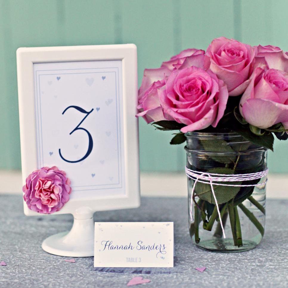 Una tarjeta de lugar de boda en un marco junto a un jarrón con rosas