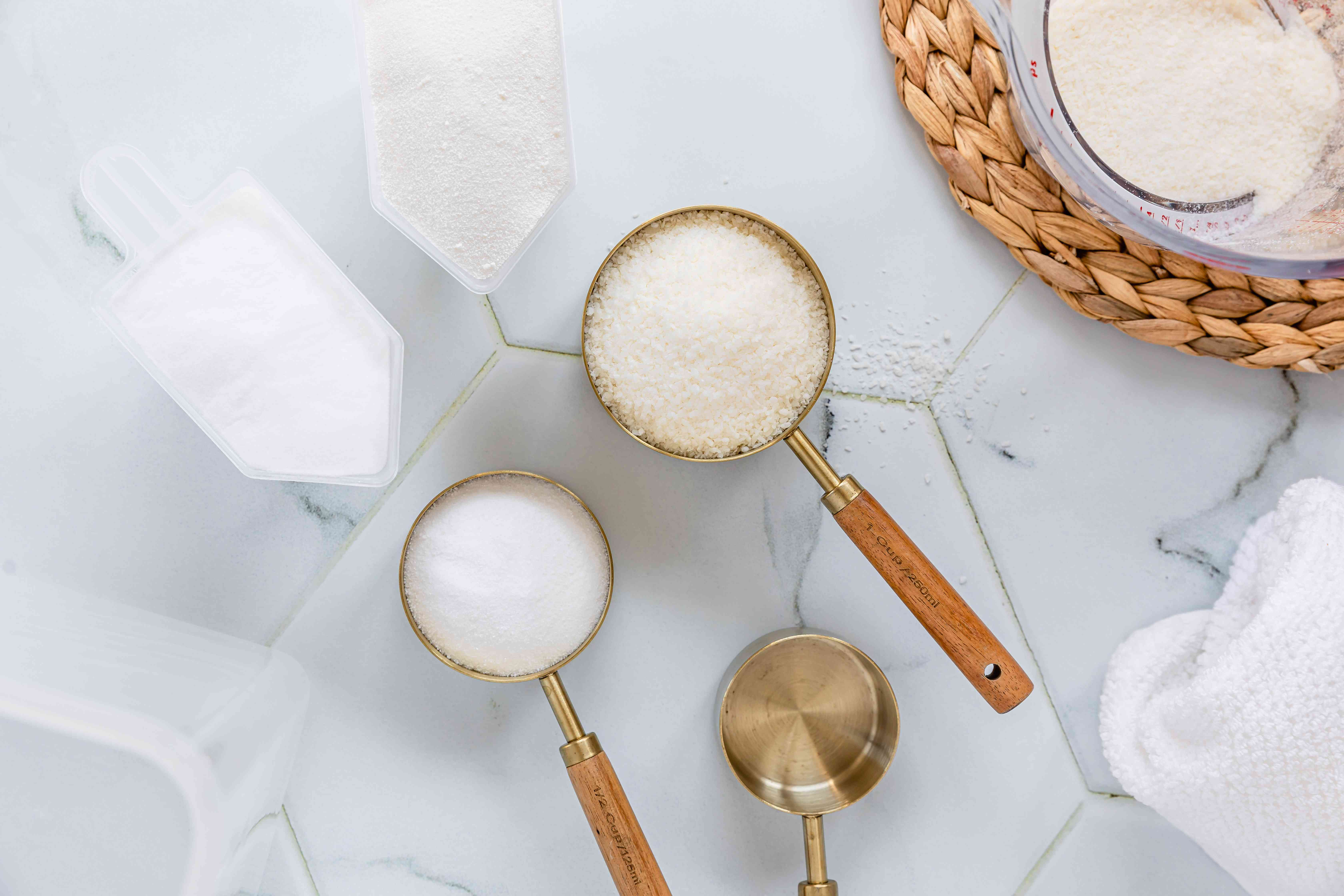 DIY powdered laundry detergent with grated soap, baking soda and borax in metal spoons
