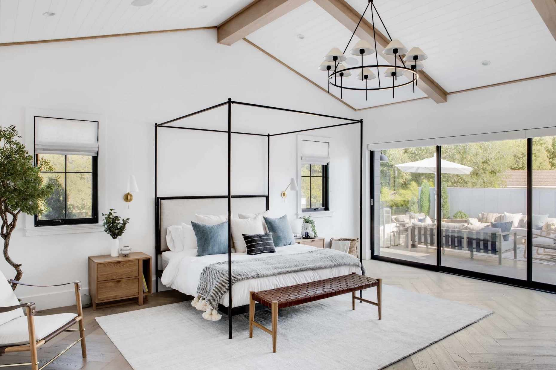 modern bedroom with black metal four poster bed frame, bonsai tree, plenty of natural lighting