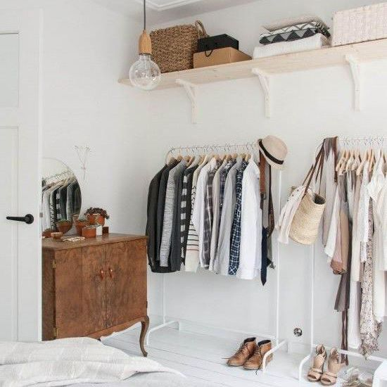 Clothing racks and shelves along one wall of a bedroom