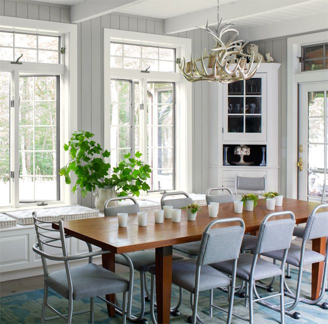 A dining room painted in Revere Pewter by Benjamin Moore with a dining table, chairs, and large windows..