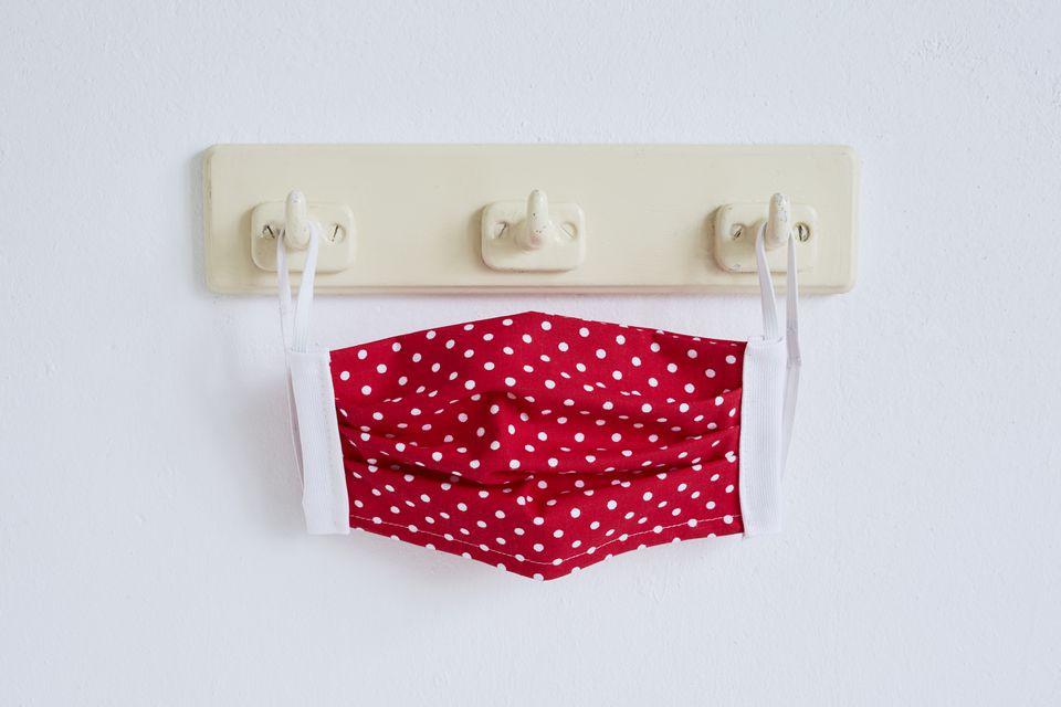 red polka dot face mask hanging on hooks