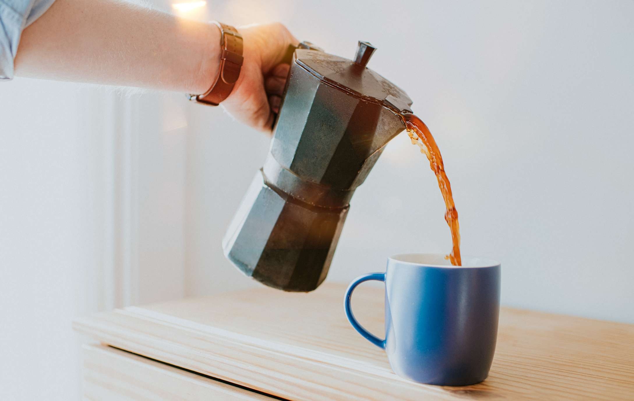 A person pouring coffee into a mug from a percolator.