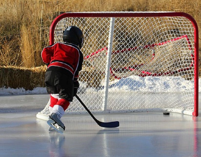 Child playing hockey -- outdoor rink