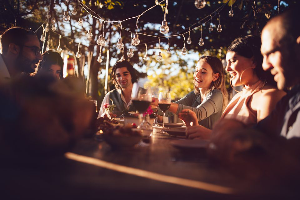 Friends celebrating with wine and food at rustic countryside party
