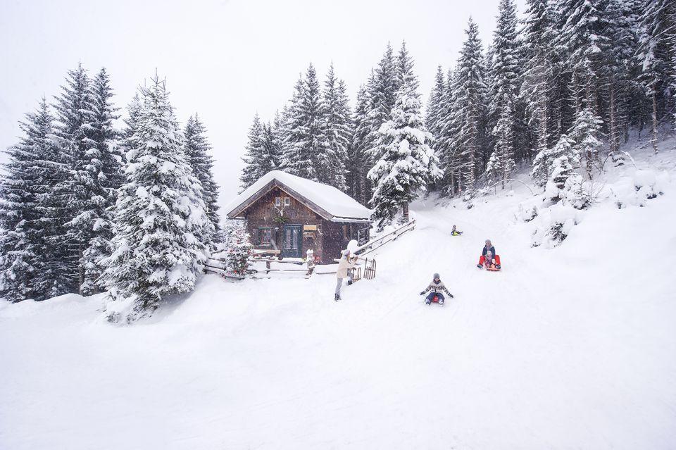 Austria, Altenmarkt-Zauchensee, familia trineo en casa de madera en Navidad