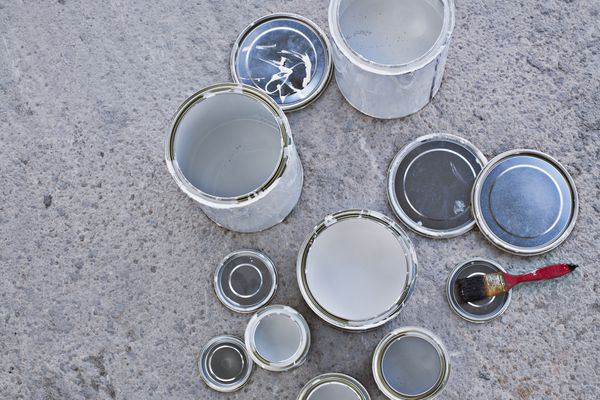 Empty paint cans and paintbrush