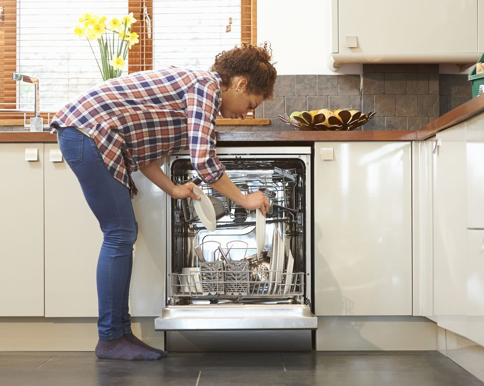 Woman unloading dishwasher in kitchen.
