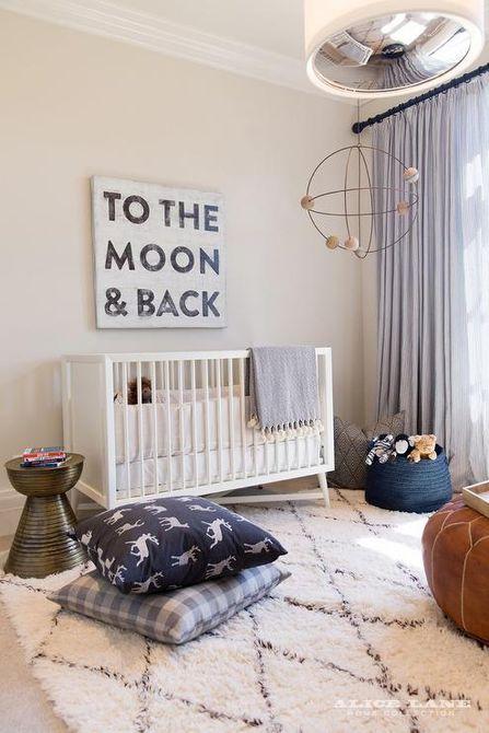 Guardería minimalista con colores neutros que incluye un letrero que dice To the Moon & Back.
