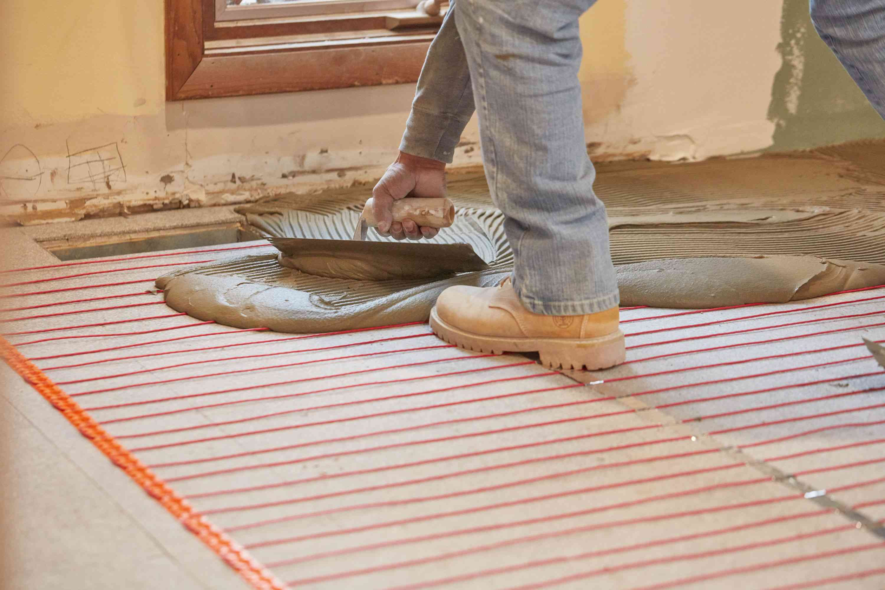 Underfloor heating system with orange wires being covered with tile mortar