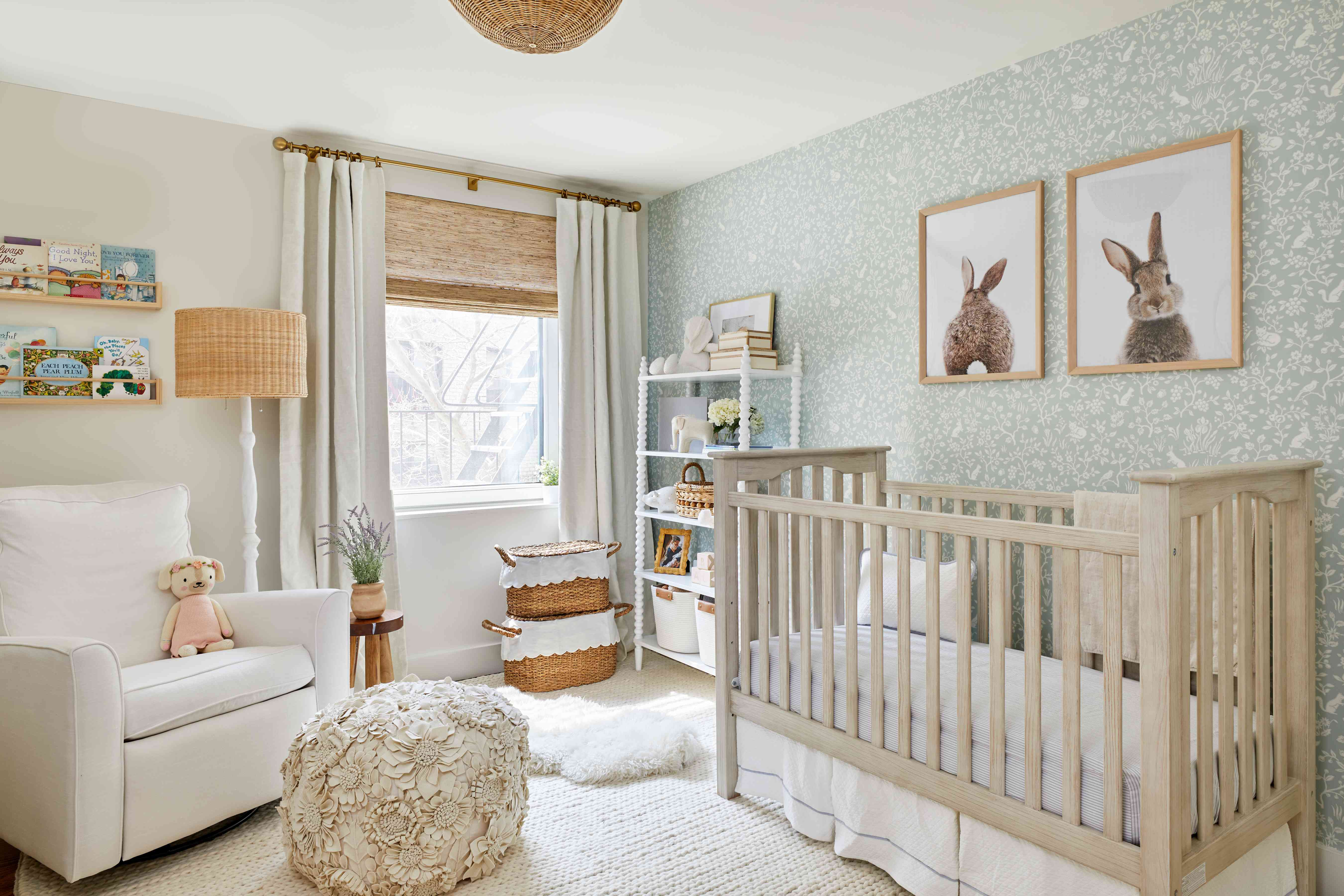 a neutral nursery room features a mint green wallpaper, white oak crib, and a white rug, drapes, bookshelves, and more
