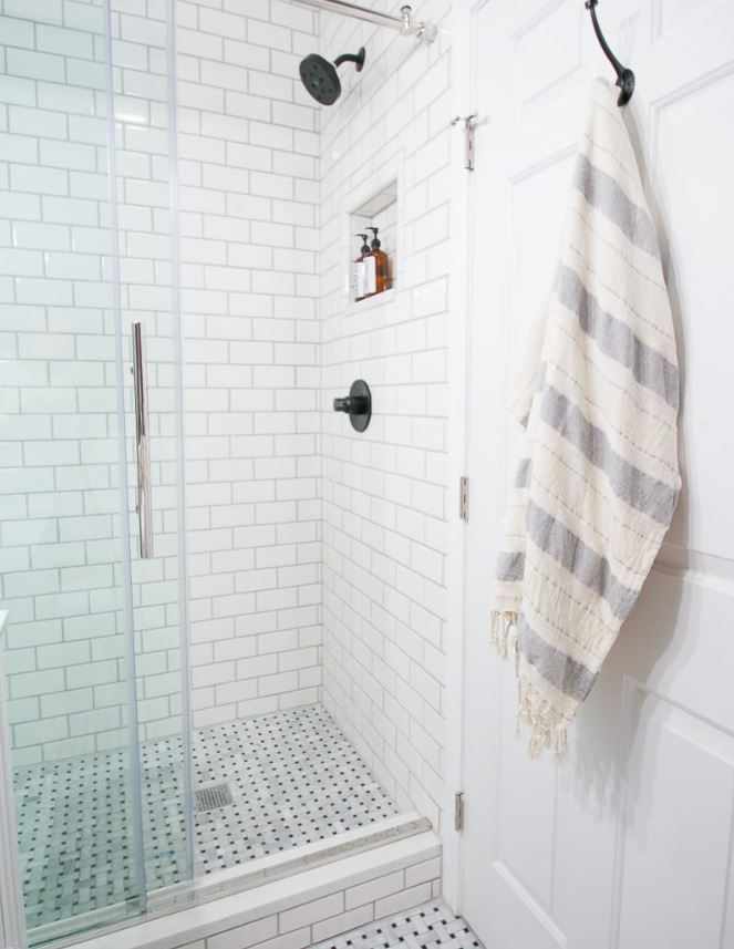 Standup shower with marble floor and subway tile walls.