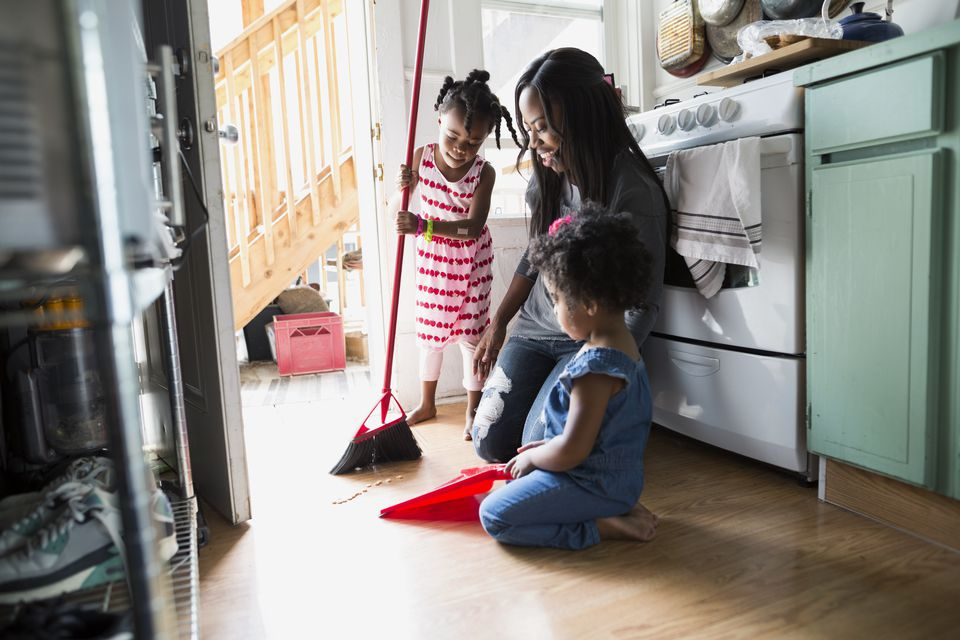 Daughters helping mother sweep kitchen floor