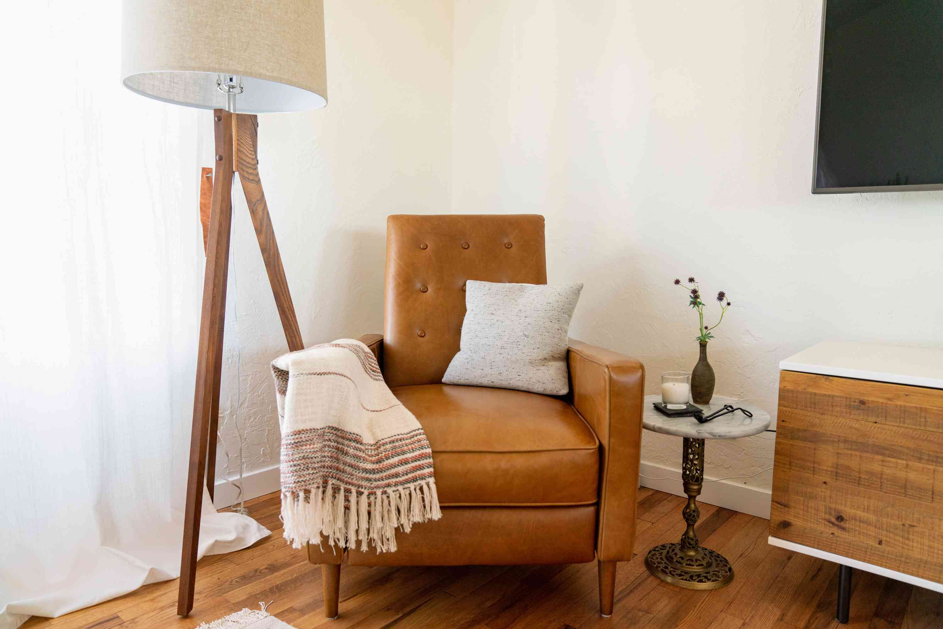Mid-century modern style brown chair with throw blanket and pillow next to floor lamp