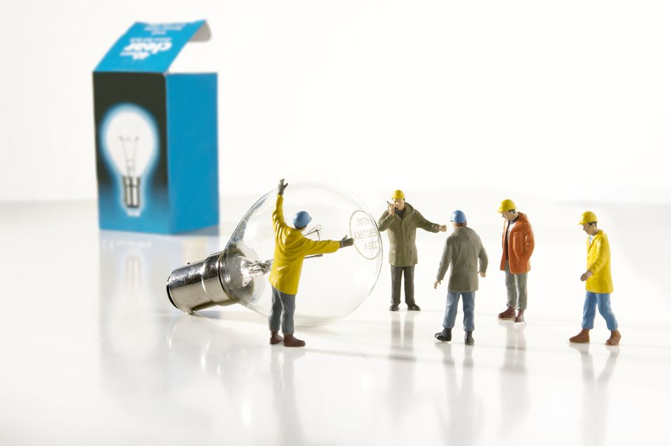 Utility worker figurines installing a light bulb