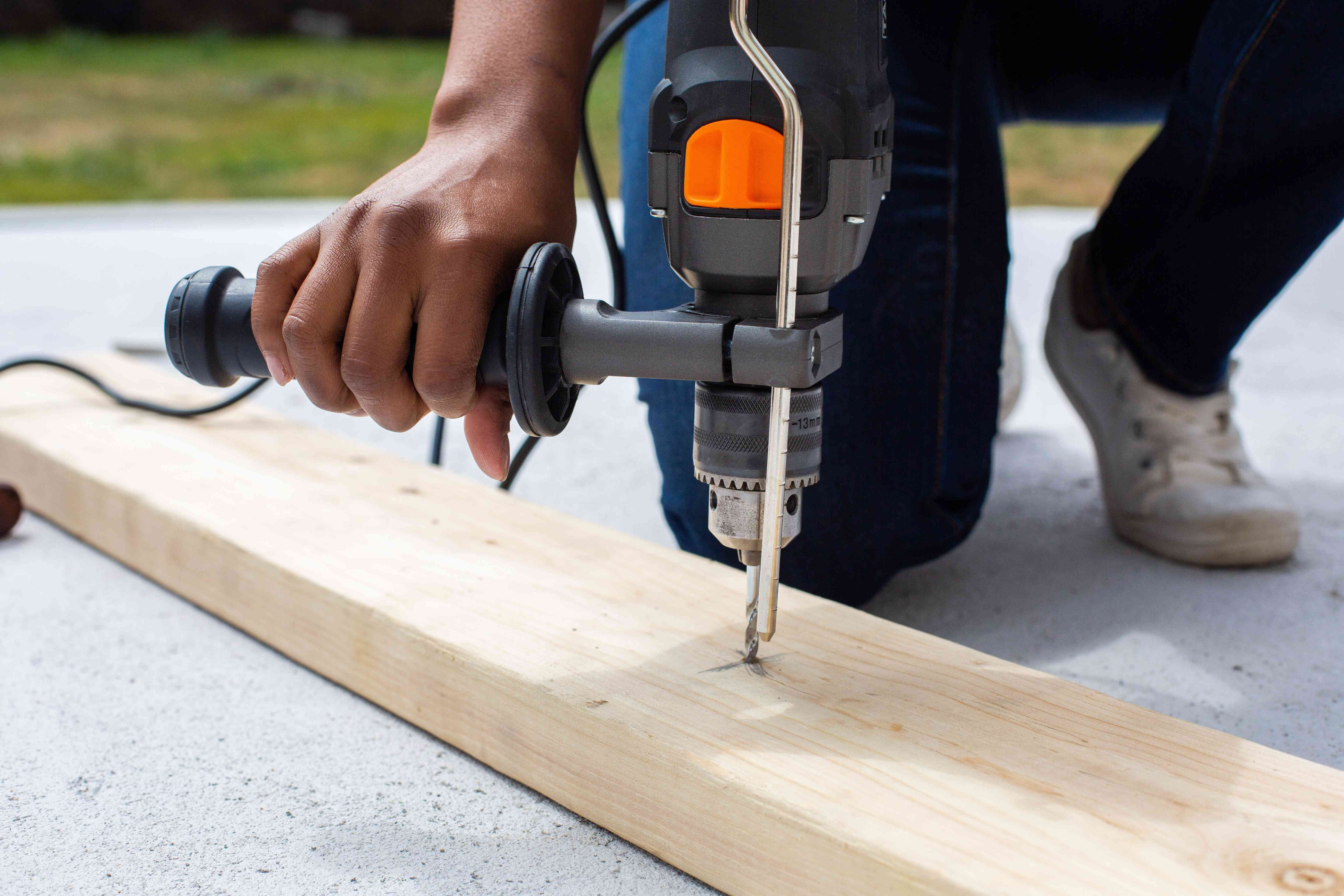 Pilot holes drilled into wood board with a hammer drill