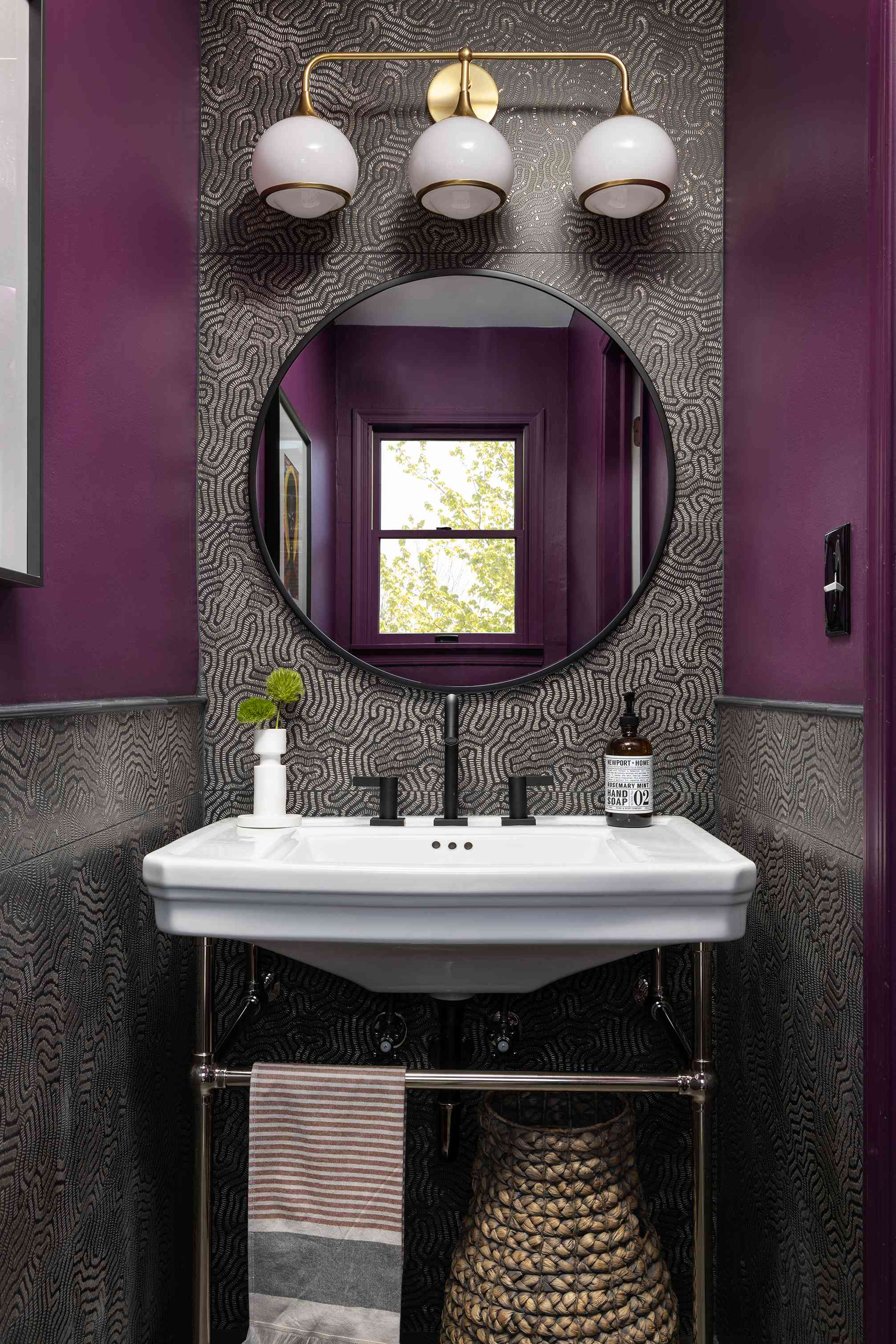 Beth Diana Smith's stunning powder room features textured tiles, purple paint, and a round mirror