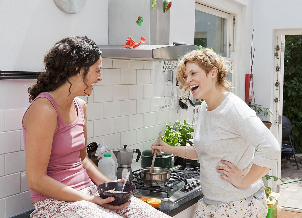 young women laughing while preparing breakfast