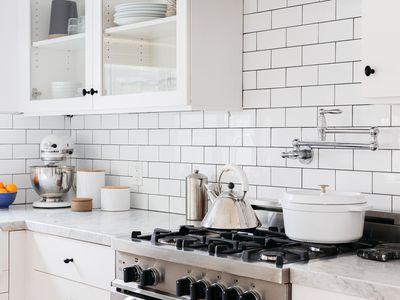 White brick backsplash in all white modern kitchen
