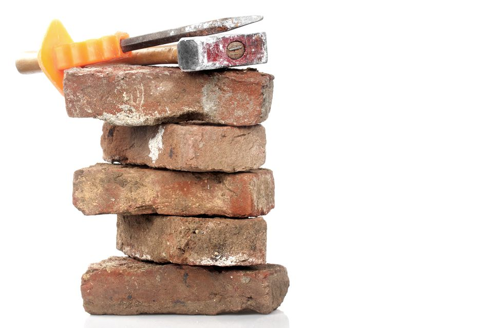 A red brick, hammer and chisel