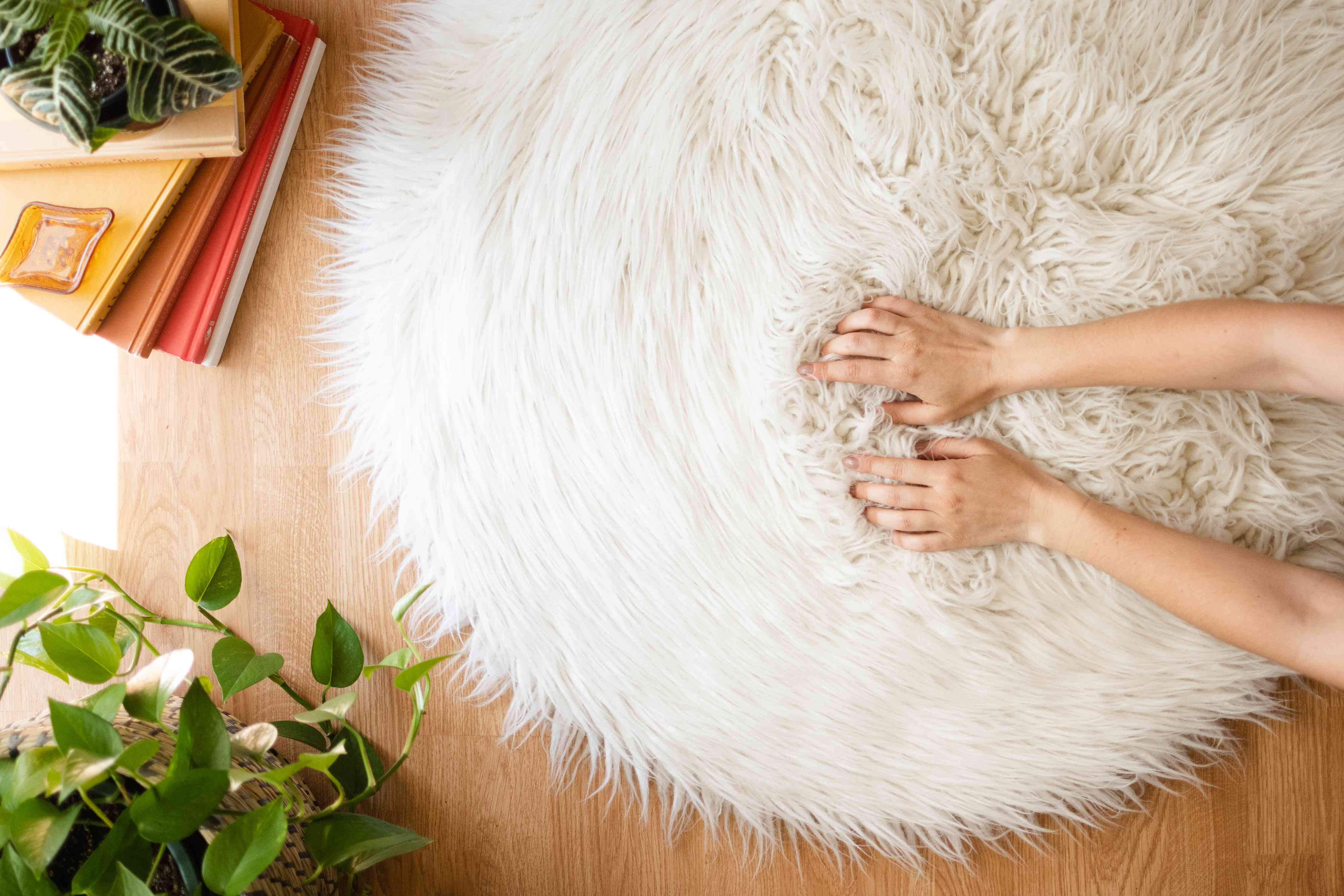 White shag rug being fluffed by hand