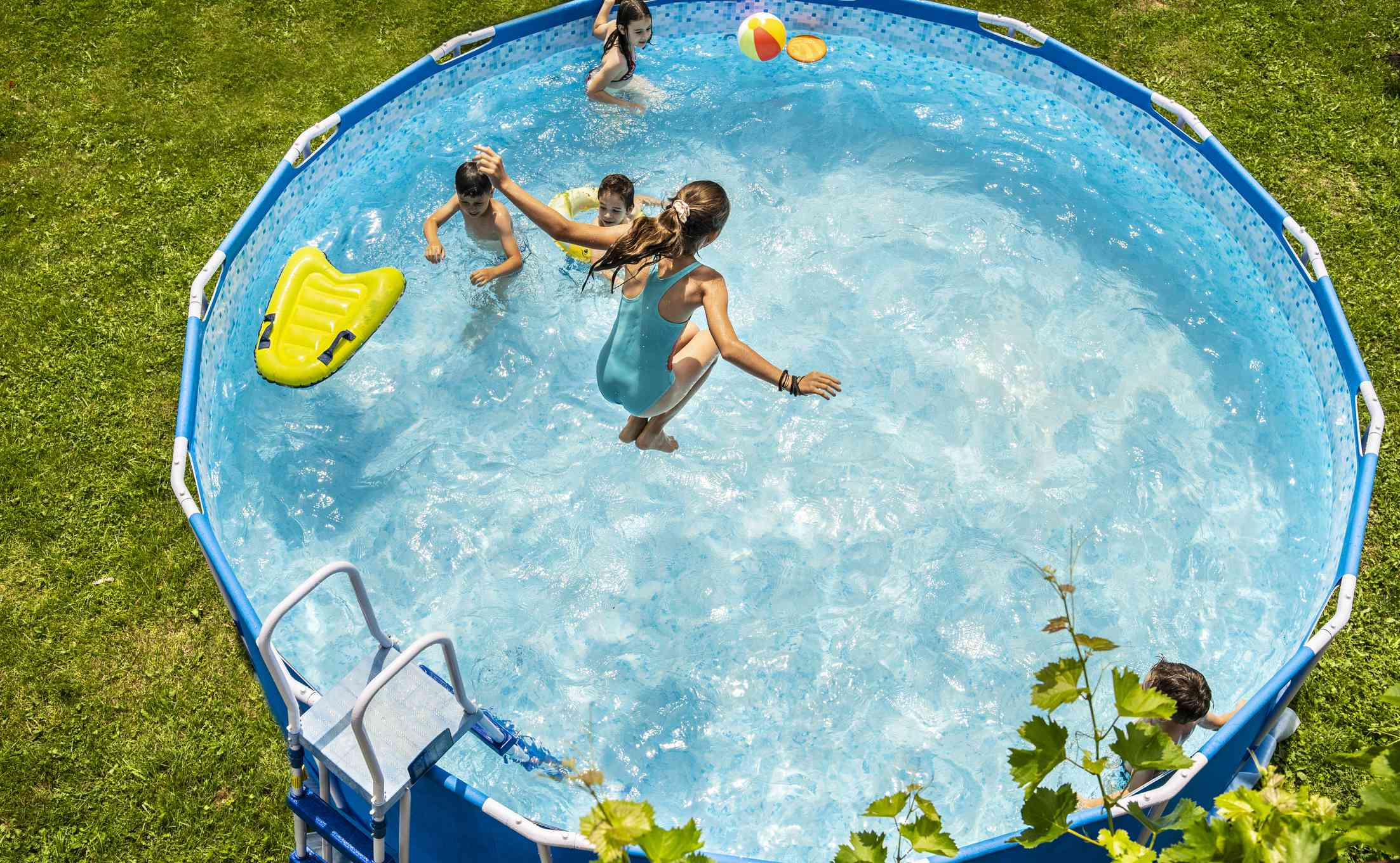 Children playing in above-ground pool