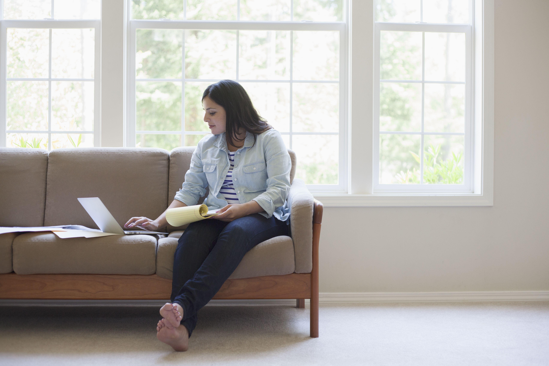 Hispanic woman using laptop on sofa