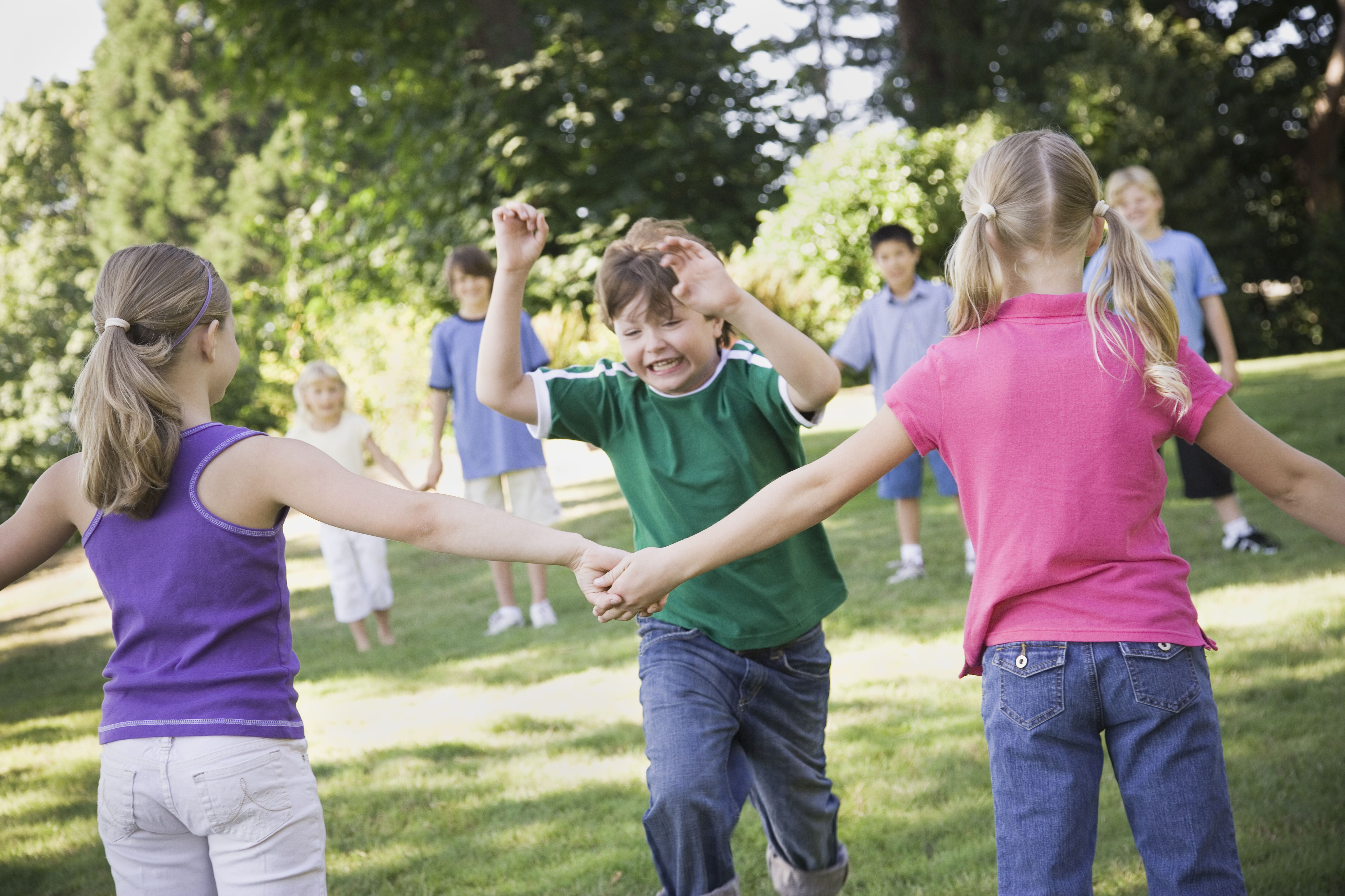Group of children (7-12) playing red rover in yard